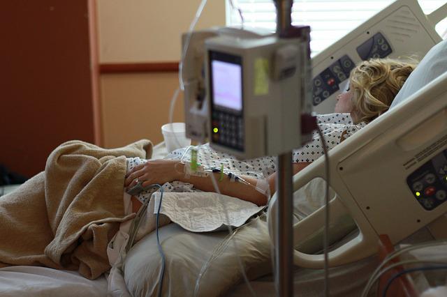 Kvinna vilar i sjukhussäng.